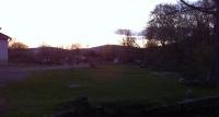 Západ slunce na pastvinou, oblaka se líně šinou.